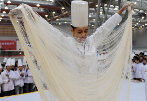 A chef demonstrates his skills at making hand-pulled noodles during a cooking competition in Hefei