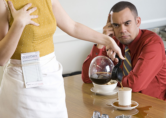 Waitress pouring coffee for man, spilling over table