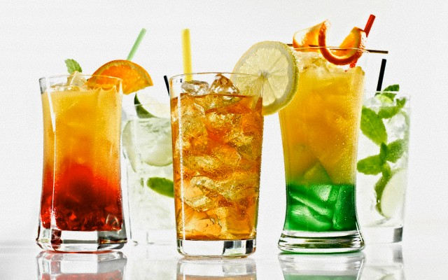 Glasses of cocktail with straw and fruit on white background --- Image by © Kai Schwabe/Westend61/Corbis