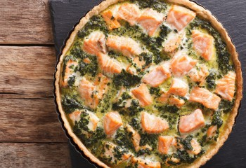 Tasty Savory Tart with salmon and spinach in the dish for baking close-up on the table. vertical view from above