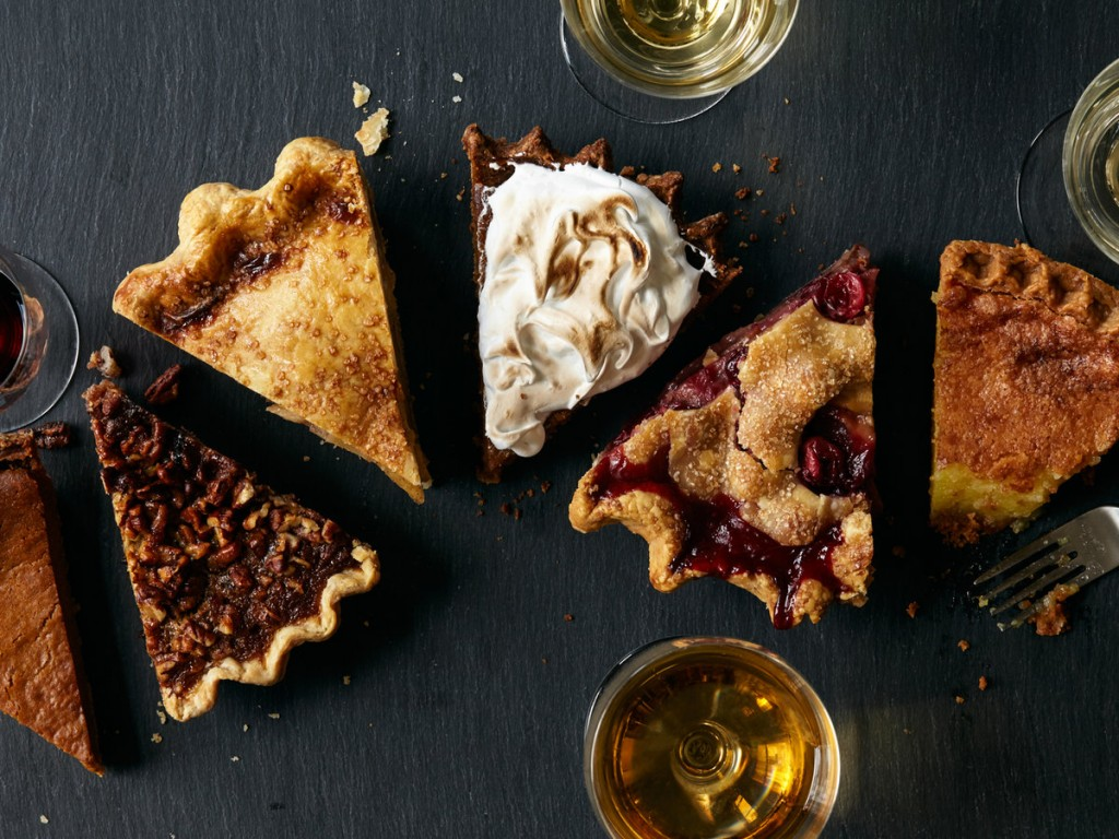 Six different slices of pie lined up, surrounded by glasses of wine, seen from above.
